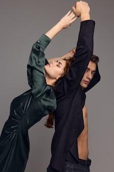 灰色の背景の男性と感情的な女性は彼らの手で身振りで示す。高品質の写真