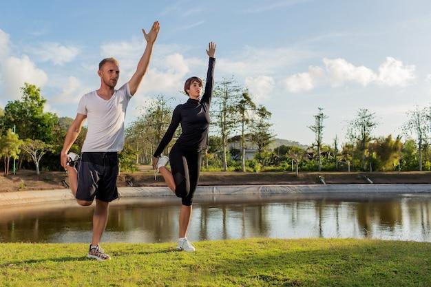 Мужчина и девушка делают разминку в парке.