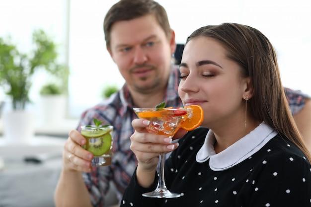 男と女は果物とアルコールカクテルを飲む