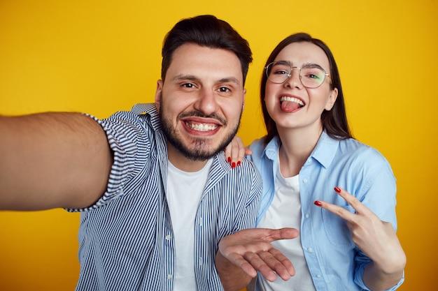 Мужчина и девушка, делающие селфи в студии, изолированные на желтом фоне