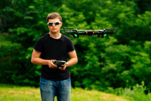 Человек и его дрон, квадрокоптер в лесу на зеленом фоне.
