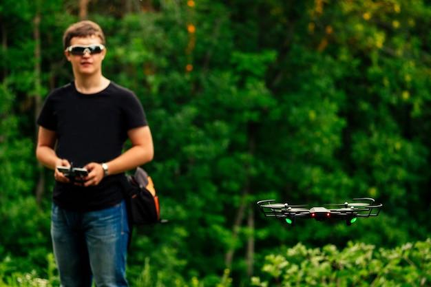 男と彼のドローン、緑の背景の森のクワッドコプター。