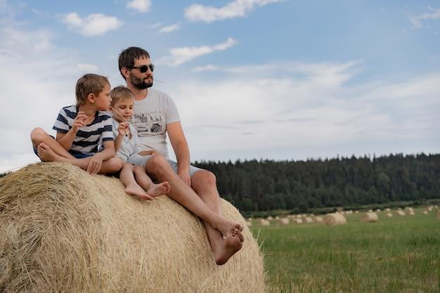Мужчина и двое его маленьких сыновей сидят на круглом стоге сена в зеленом поле в солнечный летний день Premium Фотографии