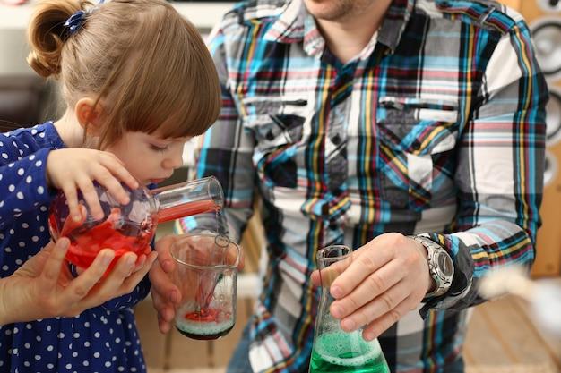 남자와 어린 소녀는 다채로운 액체와 함께 재생
