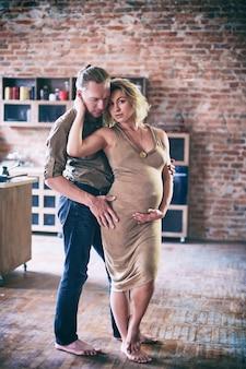 로프트 스타일 룸에서 창 근처 남자와 임신 한 여자 춤