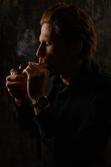 男と暗い背景の喫煙タバコスタジオの肖像画
