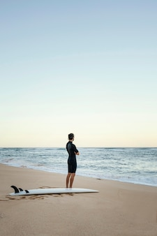 海のロングショットで男とサーフィンボード