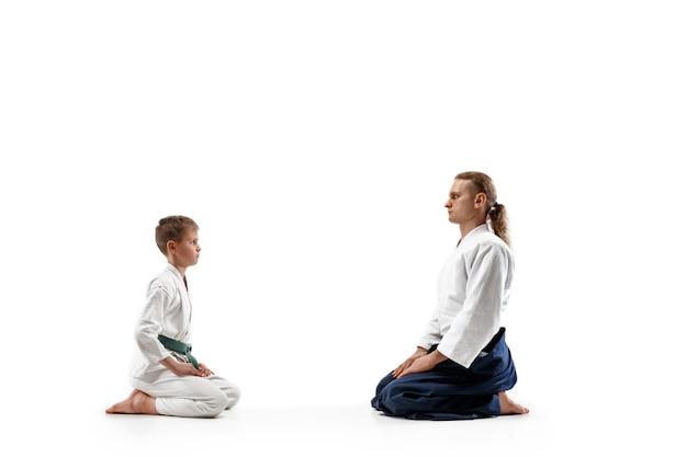 武道学校の合気道トレーニングの男と十代の少年。健康的なライフスタイルとスポーツのコンセプト。制服を着た白い着物空手男子の格闘家たち。