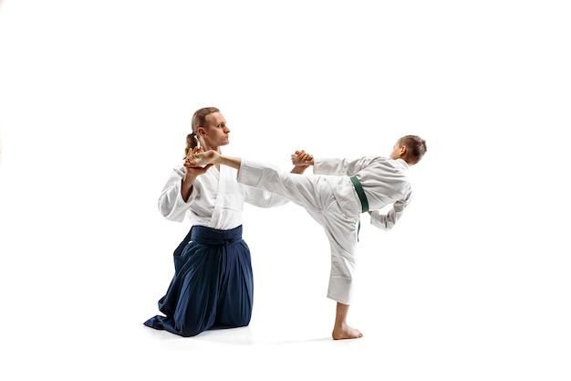 武道の学校で合気道のトレーニングで戦う男と 10 代の少年。健康的なライフスタイルとスポーツのコンセプト。白い背景に白い着物を着た戦士たち。制服を着た顔が集中する空手男子。