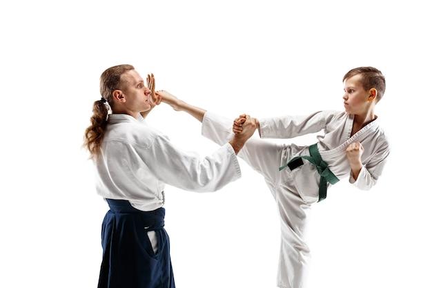 Мужчина и мальчик-подросток борются на тренировках по айкидо в школе боевых искусств. концепция здорового образа жизни и спорта. бойцы в белом кимоно на белой стене. мужчины-каратэ с сосредоточенными лицами в форме.