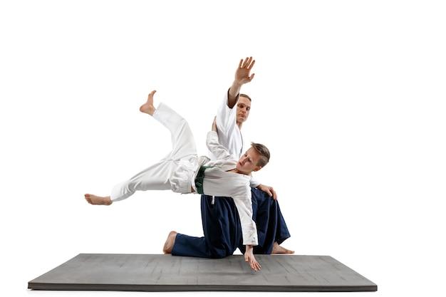 武道学校の合気道訓練で戦う男と十代の少年。健康的なライフスタイルとスポーツのコンセプト。白い壁に白い着物を着た戦闘機。制服を着た顔が集中した空手男子。
