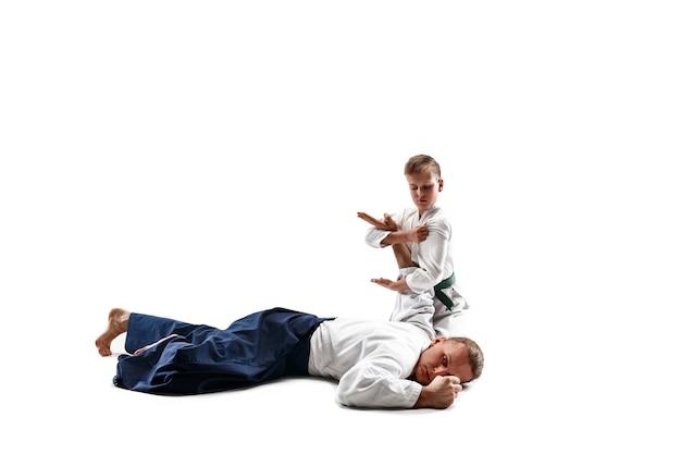 武道学校の合気道トレーニングで戦う男と十代の少年