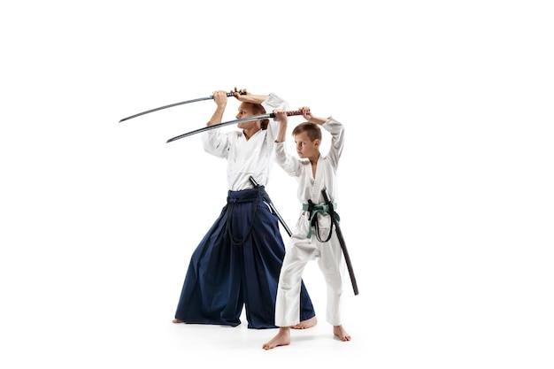 武道学校の合気道トレーニングで戦う男と十代の少年 無料写真