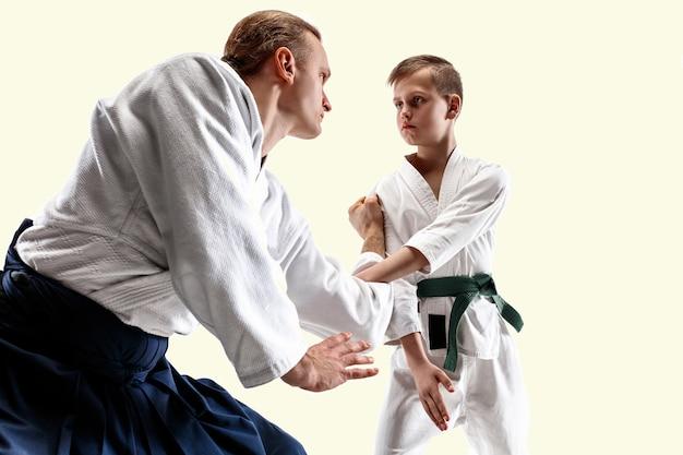무술 학교에서 합기도 훈련에서 싸우는 남자와 십 대 소년