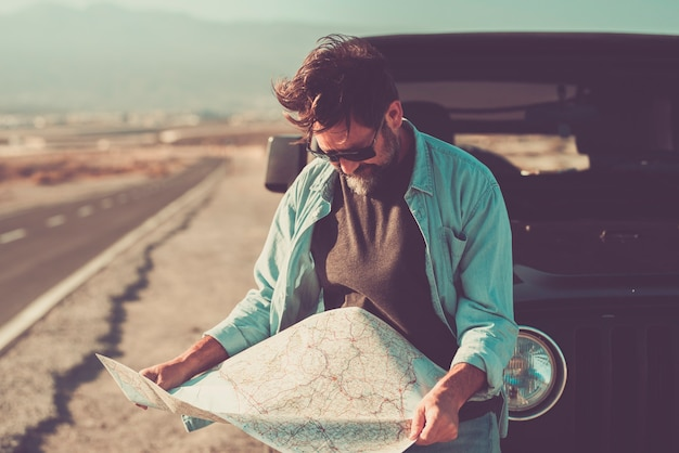 車の輸送コンセプトを持つ男性と旅行者-自動車の外で紙の地図を見る成人男性-背景の長いアスファルト道路-目的地の選択