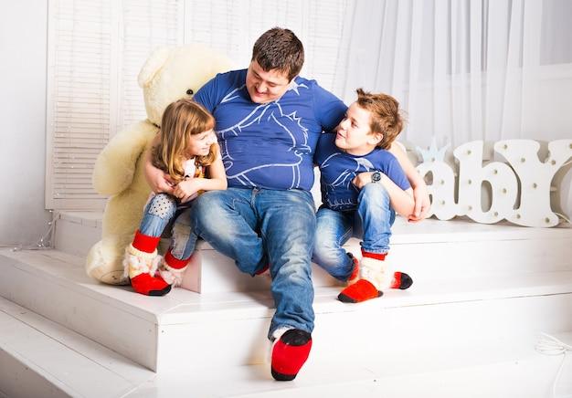 男と2人の子供が笑顔でリビングルームに座っています。