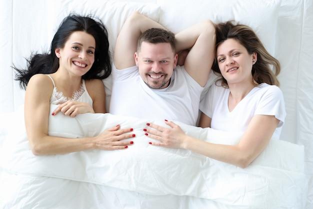 남자와 침대 평면도에 누워 두 여자. 무차별 섹스 개념
