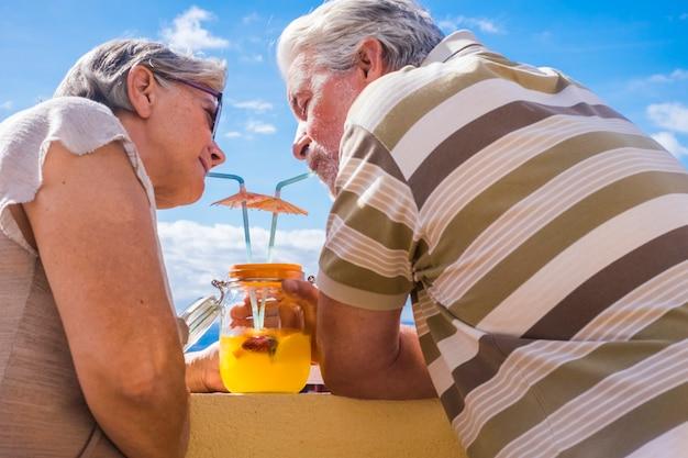 남자와 여자 성인 60 세 테라스에서 야외 꽃병 유리에서 건강한 과일 주스를 마시는. 멋진 전망과 아름다운 사람들.