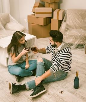 Мужчина и женщина с радостью отмечают переезд в недавно снятую квартиру