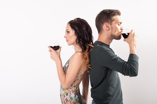 男と女はコピースペースと白い背景の上の暗いビールのグラスを保持しています。