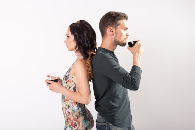 男と女は白い背景の上の暗いビールのグラスを保持しています。 。