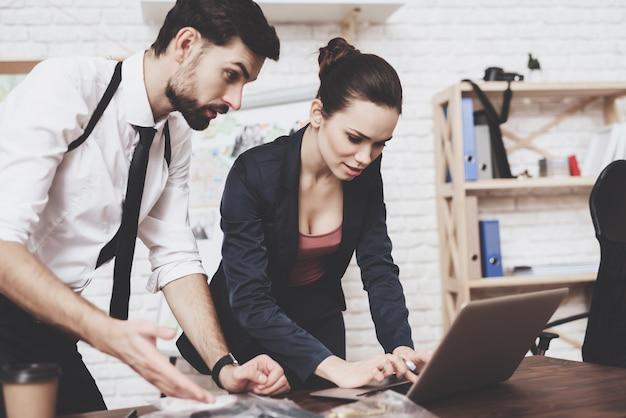 남자와 여자는 노트북에 실마리를 찾고 있습니다.