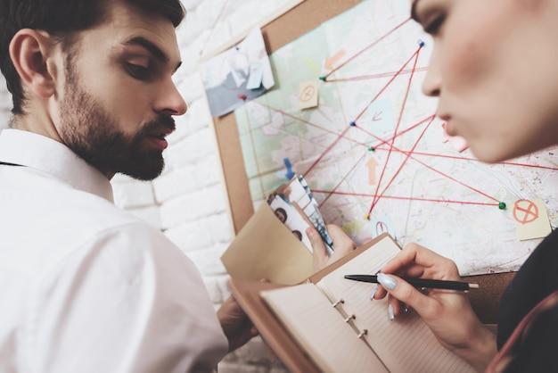 남자와 여자는 단서를 논의하면서지도를보고 있습니다.