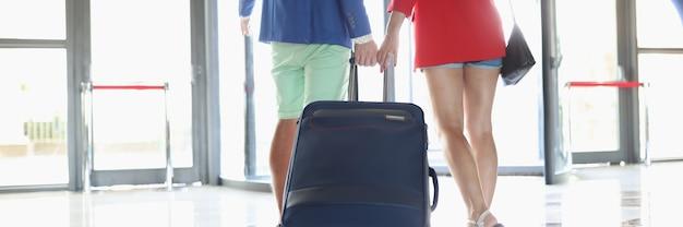 남자와 여자가 건물 출구를 향해 가방을 굴리고 있다