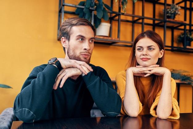 Мужчина и женщина сидят в кафе за столом и жестикулируют руками друзей, эмоции, веселый интерьер. фото высокого качества