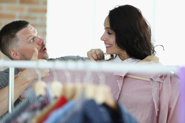Мужчина и женщина улыбаются друг другу рядом с вешалкой с вещами