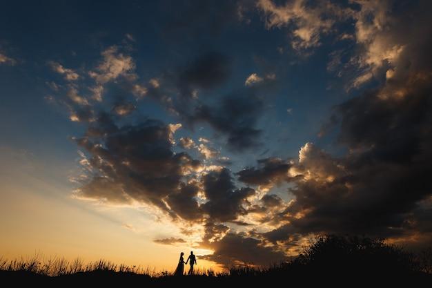 남자와 여자는 아름다운 일몰 하늘을 배경으로 필드에 걷고있다