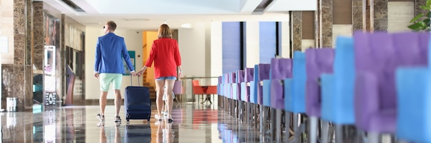 남자와 여자는 호텔 주위에 여행 가방을 들고 걷고 있다