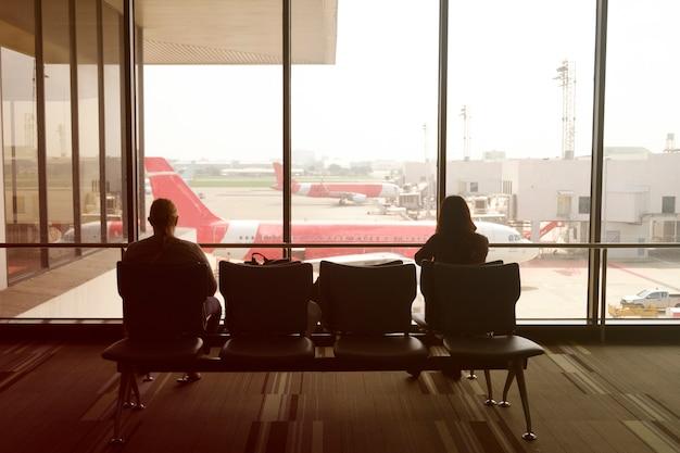 Мужчина и женщина в аэропорту, ожидая отъезда, цветное изображение фильтра, деловые поездки в аэропорт