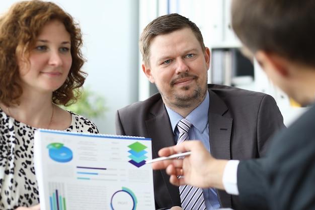 Мужчина и женщина на деловой встрече с партнером изучают документ с портретом диаграммы