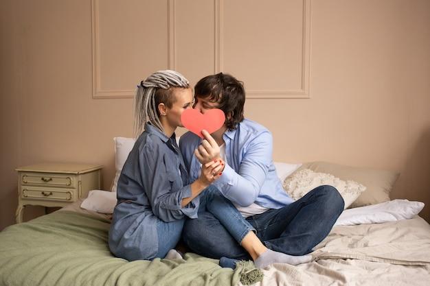 手に赤いハートのバレンタインとキスをしている家の男女。聖バレンタインの日を祝います。