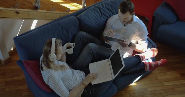 パッドとラップトップを使用して自宅で男性と女性