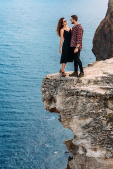 Мужчина и женщина на море, вертикальное фото. свадебное путешествие. мужчина и женщина путешествуют. пара объятий. пара поцелуев. молодожены. любители. праздничный роман. копировать пространство