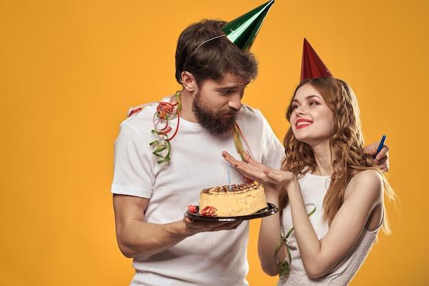 男性と女性の誕生日のお祝いケーキの黄色いスペースとheadvのキャップ。