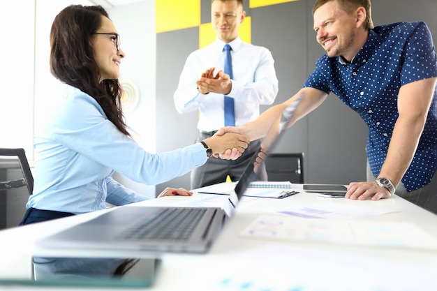 男性と女性のビジネスマンは、オフィスの肖像画のラップトップでテーブルで握手します。