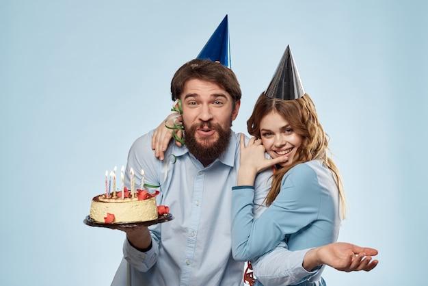 男と女は青い背景の上のケーキと帽子で誕生日を祝う