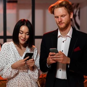 Мужчина и женщина проверяют свои телефоны на новогодней вечеринке