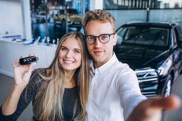 남자와 여자는 자동차 쇼룸에서 자동차를 선택