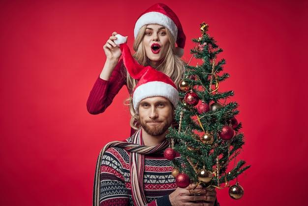 男と女のクリスマス服ホリデーギフト赤い背景