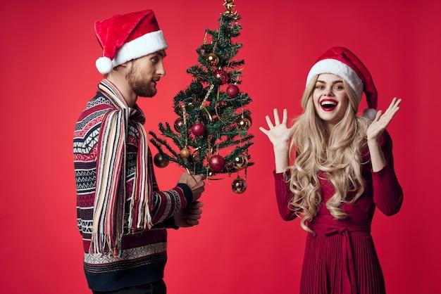 남자와 여자 크리스마스 트리 장난감 선물 휴일 빨간색 배경. 고품질 사진