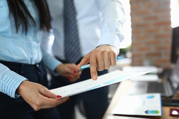 Коллеги мужчина и женщина изучают документ с расписанием на рабочем месте в офисе компании крупным планом