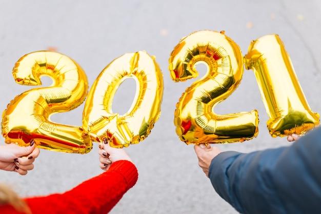 金箔風船数字2021を保持している男性と女性のカップルの手。新年のお祝いのコンセプト。
