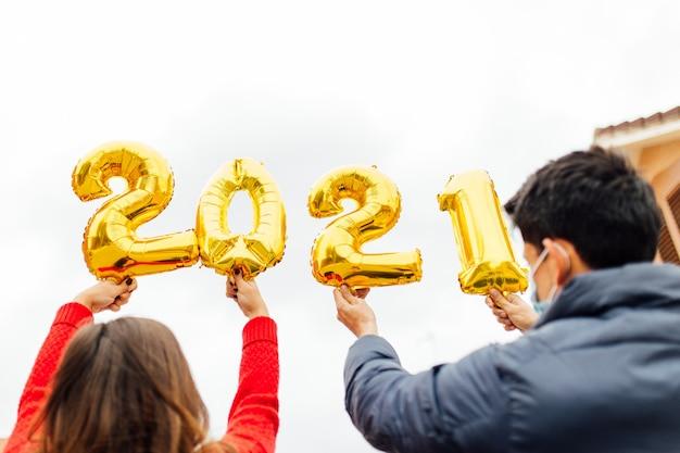 金箔風船数字2021を保持している男性と女性のカップル。新年のお祝いのコンセプト。
