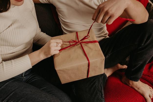 Влюбленная пара мужчина и женщина открывают подарочные коробки, развязывая лук возле елки.