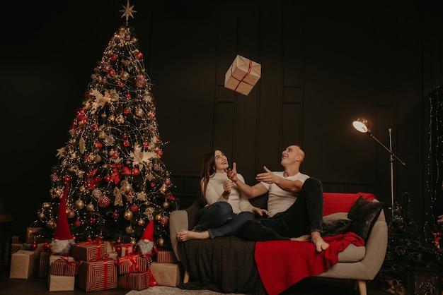 Влюбленная пара мужчина и женщина открывают подарочные коробки, развязывая бант возле елки