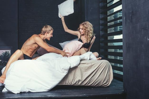Мужчина и женщина пара в нижнем белье в спальне красивой молодой счастливой и сексуальной на кровати